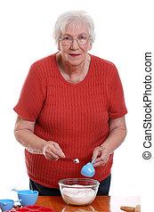 senior woman measuring while baking