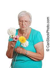 Senior woman sorting flowers - isolated Senior woman sorting...