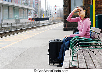 woman sitting looking for train - woman sitting on bench...