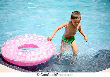 young boy playing in a pool