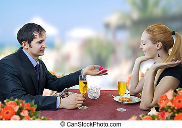Young man propose marriage to woman in restaurant - Couple...