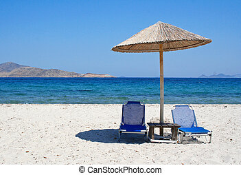 Greece. Kos island. Two chairs and umbrella on the beach -...
