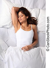 Young woman sleeping in bed - Young woman sleeping with arm...