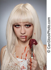 Savage girl with raw meat and blood on her