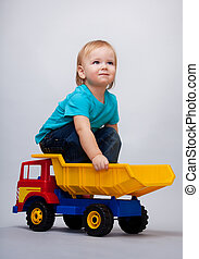 Kid sitting on a toy truck