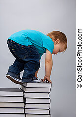 Hunger for learning - Kid climbing on top of the books pile...
