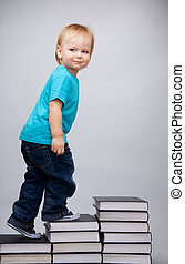 Young man climbing on a ladder of books