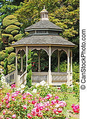 Wooden gazebo in rose garden in spring