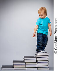 Kid on top of early education leader made of pile of books...