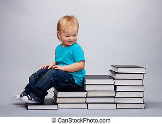 Kid sitting on a a steps made of books