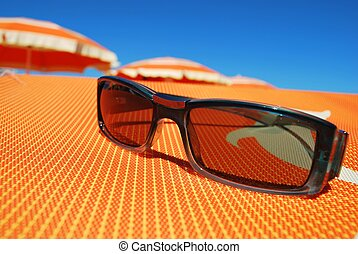 Sunglasses and beach, orange striped umbrellas in...
