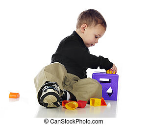 Working in 3-D - An adorable preschooler putting pieces into...