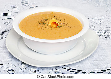 cheddar cheese soup with garnish on white lace tablecloth
