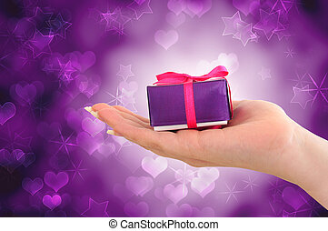 Female hand holding purple gift on starry heart background
