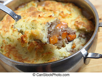 Shepherds pie on serving spoon - A serving spoon full of...