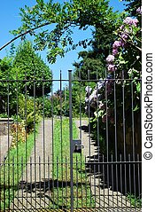 Garden gate - Closed iron garden gate with flowers and...
