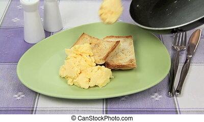 Serving Scrambled Eggs - Serving scrambled eggs from a pan...