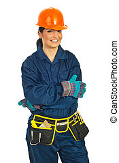 Cheerful builder woman standing with arms folded isolated on...