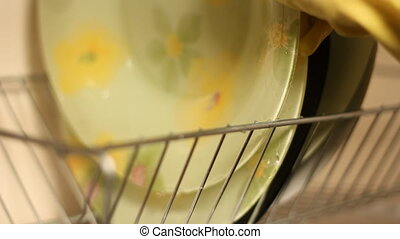 of dishes - woman washing dishes with detergent in gloves