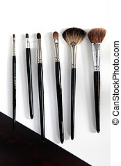 different make - up brush in a row