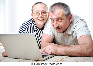 Positive elderly couple with laptop in hands