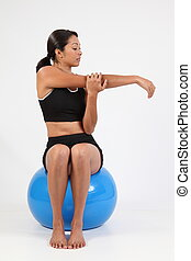 Arm stretch for girl on ball