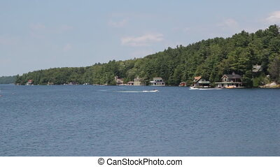 Muskoka shoreline with boat traffic - Channel of water with...