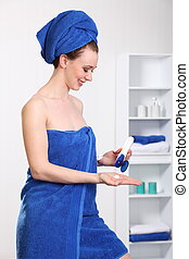 Woman applying body cream - Woman moisturising skin after a...