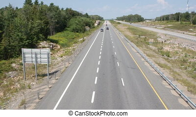 Rural highway with cars. - Cars go by on highway. Looking...