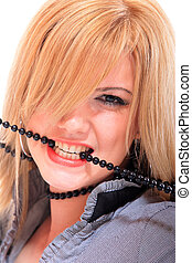 Woman open mouth and teeth biting on faux pearls