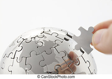 business concept with a hand building puzzle globe on white,...