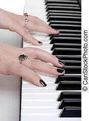 closeup hands playing a piano with black nail polish