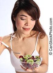 Woman eating kiwi and grapes