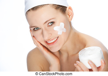 skincare - young woman with skin cream on her face