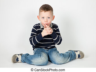 Surprised boy - The sitting boy in a striped sweater and...