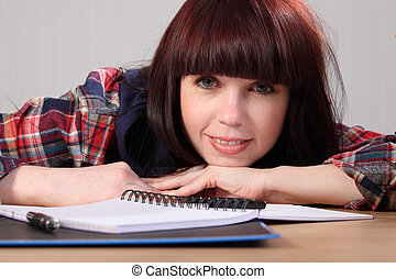 Happy young student girl takes a homework break - Beautiful...