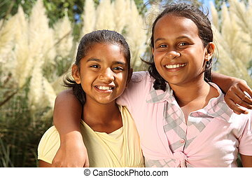 Two young girls in friendship hug - Two young school girl...
