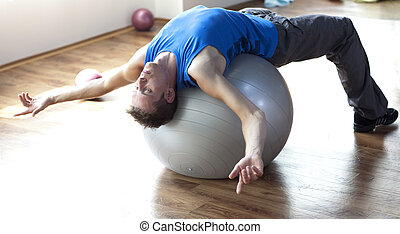 Man relaxing on large stability bal - White fit man relaxing...