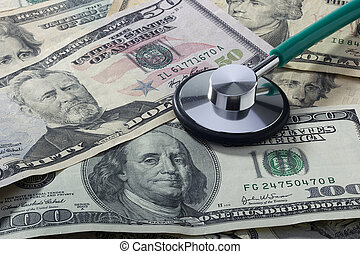 Medical Costs - Medical stethoscope laying on various...