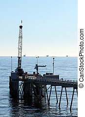 Carpinteria Pier with oil rigs at the horizon line