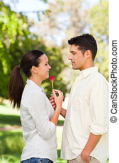 Happy man offering a rose to his gi