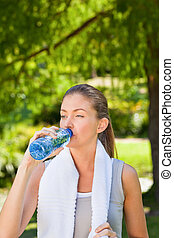 Woman drinking water after the gym