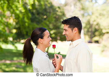 Happy man offering a rose to his girlfriend