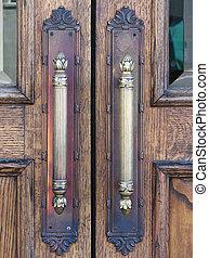 double door handles - close up of decorated vertical brass...