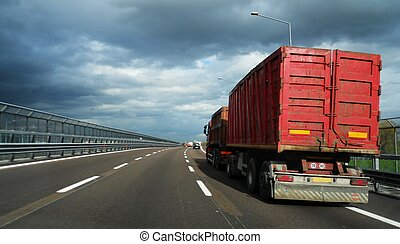 Red truck on highway under cloudy sky