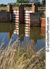 Canal sluice - Blue water in the canal and old sluice in...