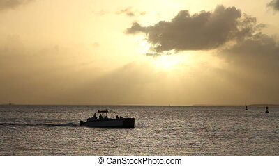 Motorboat Key West Sunset - Silhouette of motorboat passes...