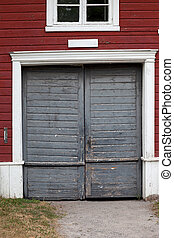 Old wooden double door with sand path