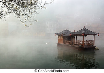 China landscape of boat on foggy river with traditional...