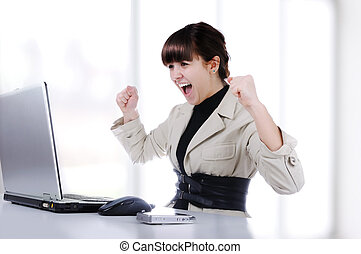 Excited young business woman with her clenched fist